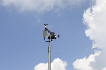 Weather station mast against blue cloudy sky