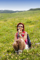 Cute woman hiker smelling herbs in the mountain