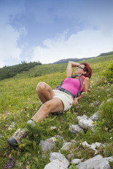 Woman hiker resting, lying high in the mountain
