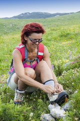 Woman hiker tying the shoelaces   in mountains