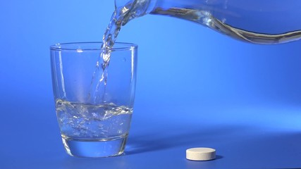 dissolving aspirin tablets in a glass of water