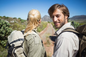 Hiking couple walking on mountain terrain man smiling at camera