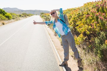 Attractive blonde hitch hiking on rural road