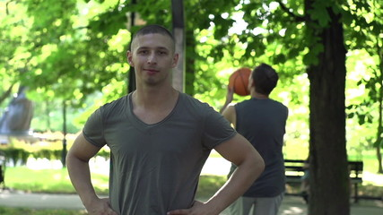Portrait of happy basketball player in park, super slow motion