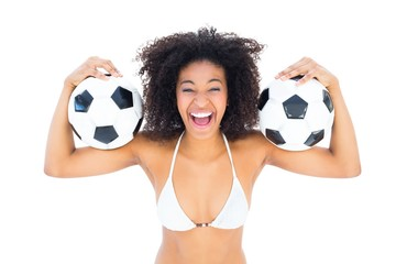 Excited fit girl in white bikini holding football