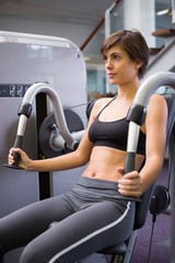 Smiling brunette using weights machine for arms