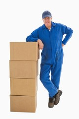 Happy delivery man leaning on pile of cardboard boxes