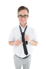 Geeky hipster fixing his tie smiling at camera