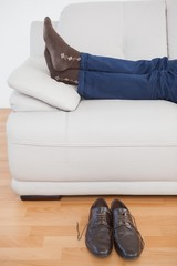 Tired businessman lying on sofa with shoes off
