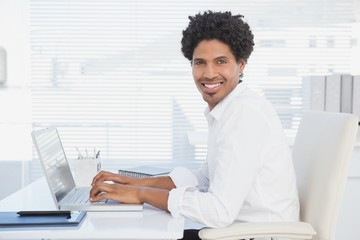 Handsome casual businessman smiling at camera working on laptop