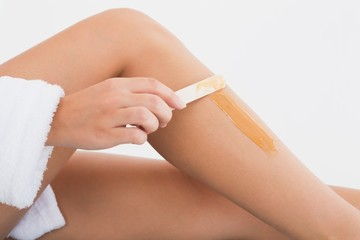 Side view of female applying hot wax on leg