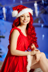 Young beauty smiling santa woman near Christmas tree. Fashionabl