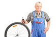 Mature mechanic standing by a bicycle wheel