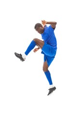 Football player in blue kicking and jumping