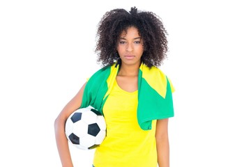 Pretty football fan holding brazilian flag looking at camera