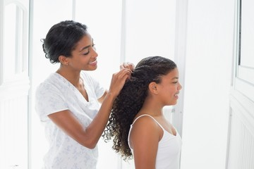 Pretty mother tying her daughters hair back
