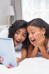 Surprised mother and daughter using tablet together