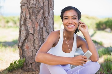 Fit woman sitting against tree listening to music