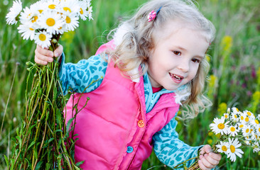 happy little girl holding a bouquet of daisies