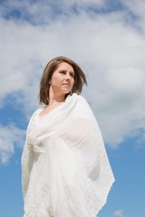 Woman looking away against blue sky and clouds