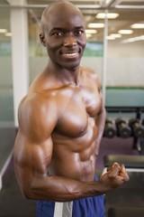 Smiling shirtless muscular man posing in gym