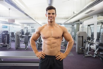 Smiling shirtless muscular man with hands on hips in gym