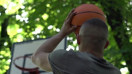 Man throw ball, score point on basketball court, super slow moti