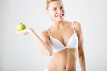 young slim woman in lingerie holding a green apple