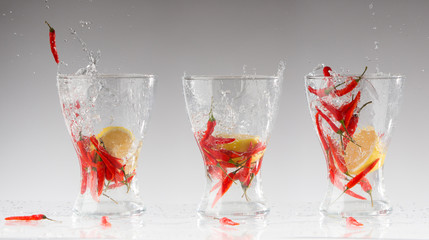 splashes of water from the red hot pepper and lemon in a glass.