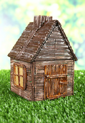 Small wooden house on grass on bright background
