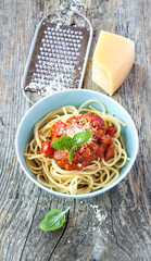 Spaghetti bolognese in blue bowl on vintage rustic wood