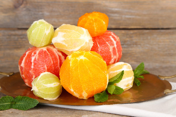Citrus fruits without skin on tray, on wooden background