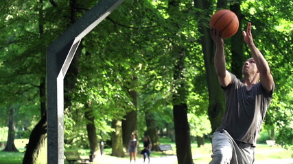 Man playing basketball on court in park, super slow motion,