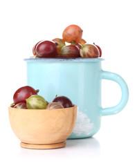 Ripe gooseberries in mug isolated on white.