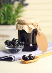 Ripe blackcurrants in bowl and glass jar with tasty jam