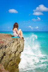 beautiful girl sitting on a rock looking at the sea ocean