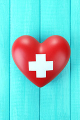 Red heart with cross sign on color wooden background