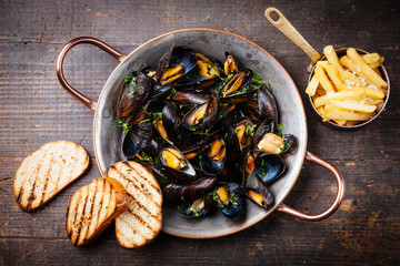 Mussels in copper cooking dish and french fries on dark wooden b