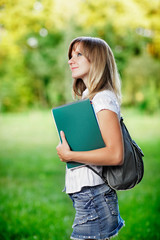 Young female student  standing on green blurred grass background