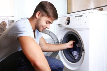 Housework: Man loading clothes into washing machine