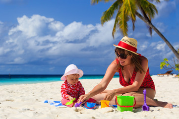 mother and daughter playing on tropical beach