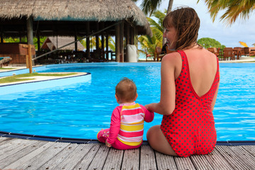 mother and little daughter sitting on pool