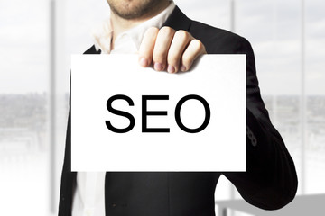 businessman holding sign seo