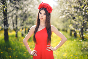 Young pretty girl posing in summer field with flowers