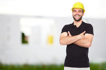 Young smiling builder standing before building