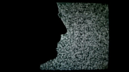 Unshaven man profile silhouette in front of static TV noise