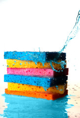 Mulit Colored Sponges Stacked on top of one another with Splash