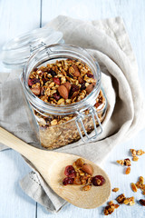 Granola in a glass jar on a light wooden background