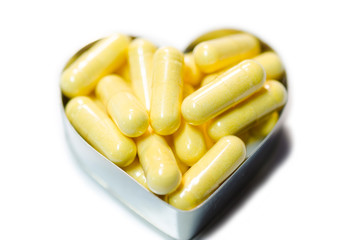 yellow food supplemnet CoQ10 (Co-enzyme Q10) capsules in heart s