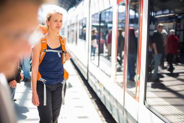 Pretty, young woman in a trainstation, waiting for her train